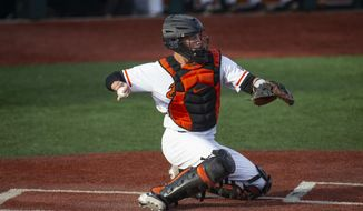 In this April 26, 2019, file photo, Adley Rutschman catches for Oregon State during an NCAA college baseball game against Washington State in Corvallis, Ore. The Baltimore Orioles lead off the Major League Baseball Draft for the first time in 30 years and Oregon State catcher Adley Rutschman is a heavy favorite to be selected No. 1 on Monday night, June 3, 2019. (AP Photo/Chris Pietsch, File) **FILE**