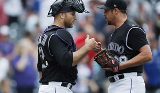 Colorado Rockies catcher Chris Iannetta, left, congratulates relief pitcher Bryan Shaw after he struck out Toronto Blue Jays' Eric Sogard for the final out in the ninth inning of a baseball game Sunday, June 2, 2019, in Denver. The Rockies won 5-1. (AP Photo/David Zalubowski)