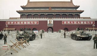 FILE - In this June 10, 1989 file photo, People's Liberation Army (PLA) troops stand guard with tanks in front of Tiananmen Square after crushing the students pro-democracy demonstrations in Beijing. Thirty years since the Tiananmen Square protests, China's economy has catapulted up the world rankings, yet political repression is harsher than ever. (AP Photo/Sadayuki Mikami, File)
