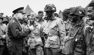 In this June 6, 1944, photo, U.S. Gen. Dwight D. Eisenhower, left, gives the order of the day to paratroopers in England prior to boarding their planes to participate in the first assault of the Normandy invasion. (U.S. Army Signal Corps via AP)