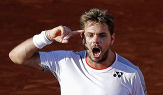 Switzerland's Stan Wawrinka celebrates winning his fourth round match of the French Open tennis tournament against Greece's Stefanos Tsitsipas in five sets, 7-6 (8-6), 5-7, 6-4, 3-6, 8-6, at the Roland Garros stadium in Paris, Sunday, June 2, 2019. (AP Photo/Christophe Ena )