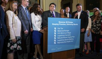 Illinois Governor J.B. Pritzker holds a press conference, surrounded by both Republicans and Democrats from the legislature, touting the accomplishments of the Spring Session after the Illinois Senate approved funding for the capital construction plan, legalized sports betting and gambling expansion, Sunday, June 2, 2019, in Springfield, Ill. (Justin L. Fowler/The State Journal-Register via AP)