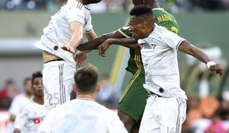 Portland Timbers' Larrys Mabiala, back right, jumps for a head ball next to Los Angeles FC's Mark-Anthony Kaye (14) and Walker Zimmerman (25) during an MLS soccer match Saturday, June 1, 2019, in Portland, Ore. (Sean Meagher/The Oregonian via AP)