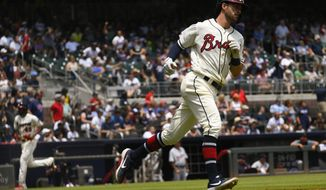 Atlanta Braves' Dansby Swanson runs the first base line as Julio Teheran, left, approaches home plate during his two-run home run in the third inning of a baseball game against the Detroit Tigers, Sunday, June 2, 2019, in Atlanta. (AP Photo/John Amis)