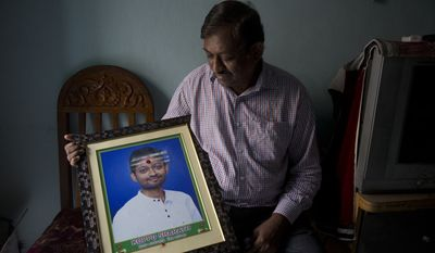 Koppu Ram Mohan, father of Indian student Sharath Koppu who was shot dead in the U.S.          holds a photograph of his son in Hyderabad, India, Tuesday, July 17, 2018. 25-year-old Koppu was shot on July 6 during an armed robbery at a fast food restaurant in Kansas City where he worked. Authorities say a gunman being investigated in the killing of the university student from India shot and wounded three Kansas City police officers Sunday before dying in an exchange of gunfire with police. (AP Photo/Mahesh Kumar A.)