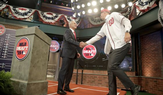 Major League Baseball Commissioner Rob Manfred, left, greets Jackson Rutledge, a right-handed pitcher from San Jacinto Junior College in Pasadena, Texas, onstage after Rutledge was elected No. 17 by the Washington Nationals in the first round of the Major League Baseball draft, Monday, June 3, 2019, in Secaucus, N.J. (AP Photo/Julio Cortez)