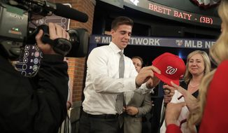 Jackson Rutledge, a right-handed pitcher from San Jacinto Junior College in Pasadena, Texas, receives a cap after being selected No. 17 by the Washington Nationals in the first round of the Major League Baseball draft, Monday, June 3, 2019, in Secaucus, N.J. (AP Photo/Julio Cortez) ** FILE **