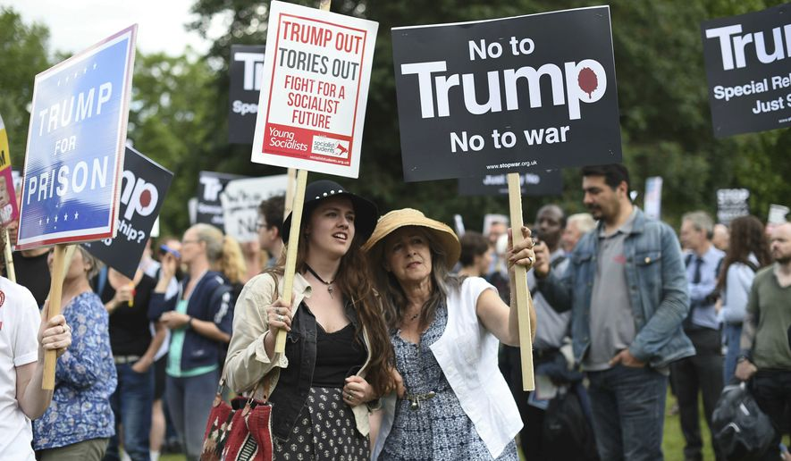 Protestors gather outside Buckingham Palace, during the first day of a state visit by US President Donald Trump, in London, Monday June 3, 2019. (David Mirzoeff/PA via AP)