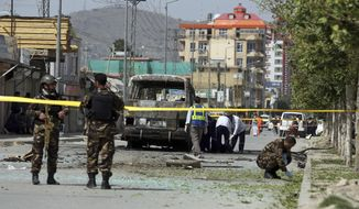 Health workers evacuate a body as security personnel collect evidence after an attack that targeted a bus carrying government employees in Kabul, Afghanistan, Monday, June 3, 2019. Afghan officials said a sticky bomb attached to the bus detonated in the capital. Wahidullah Mayar, spokesman for the public health ministry, said five people were killed and 10 wounded in initial casualty reports and could rise. (AP Photo/Rahmat Gul)