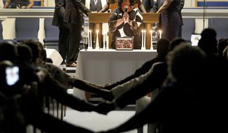 After lighting 12 candles, Veronica Coleman leads the congregation in prayer during a vigil for Ryan Keith Cox at the Piney Grove Baptist Church in Virginia Beach, Va., Sunday June 2, 2019. Cox was killed while trying to help people during the mass shooting at the Virginia Beach Municipal Center several days earlier. (Rob Ostermaier/The Virginian-Pilot via AP)