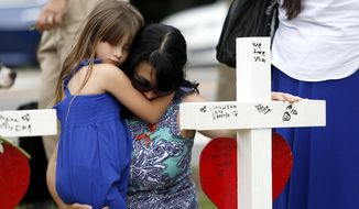 Del. Kelly Fowler holds her daughter Sophie, 6, in front of the row of crosses at the memorial located by Building 11 of the Virginia Beach Municipal Center, Sunday, June 2, 2019, in Virginia Beach, Va. Twelve crosses were placed at the memorial to honor the 12 victims of the mass shooting that took place at the center several days earlier. (Sarah Holm/The Virginian-Pilot via AP)
