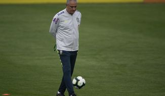 Brazil's national soccer team coach Tite kicks the ball during a practice session at the Granja Comary training center ahead the Copa America tournament in Teresopolis, Brazil, Sunday, June 2, 2019. (AP Photo/Leo Correa)