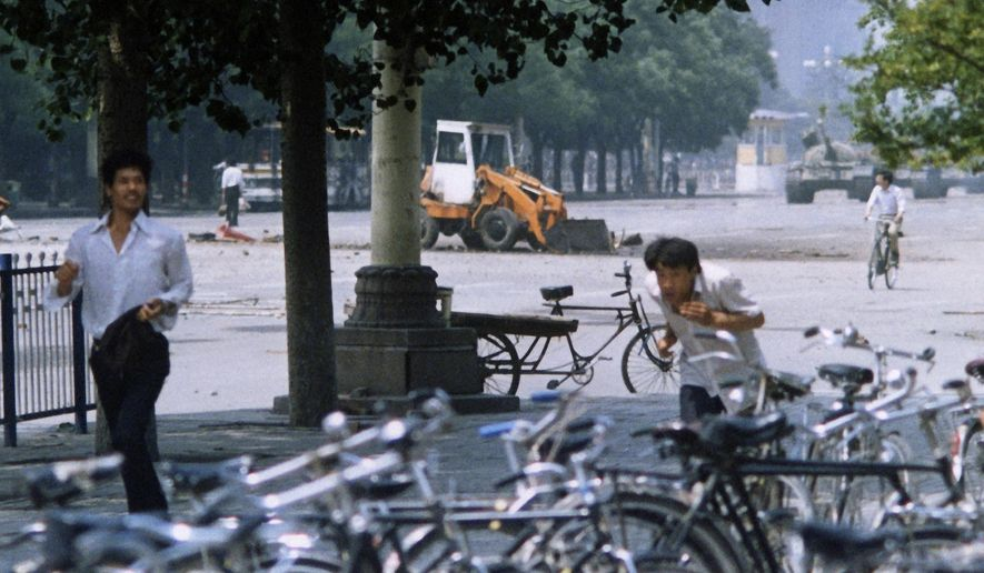 FILE - In this June 5, 1989, file photo, three unidentified men flee the scene, as a Chinese man, background left, stands alone to block a line of approaching tanks, background right, in Beijing's Tiananmen Square. The man in the background stood his ground and blocked the column of tanks when they came closer, an image captured on film by numerous other photographers and one that ultimately became a widely reproduced symbol of events there. (AP Photo/Terril Jones, File)