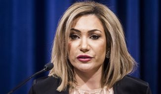 FILE--In this Thursday, Feb. 21, 2019, file photo, Solicitor General Fadwa Hammoud speaks during a press conference at the Frank Kelley Law Library in the Williams Building in Lansing, Mich. Authorities investigating Flint's water crisis have seized from storage the state-owned mobile devices of Snyder and 65 other current or former officials. Hammoud and Wayne County Prosecutor Kym Worthy confirmed they executed a series of search warrants related to the criminal investigation of Flint's lead-contaminated water and a deadly outbreak of Legionnaires' disease. (Jake May/The Flint Journal via AP, File)