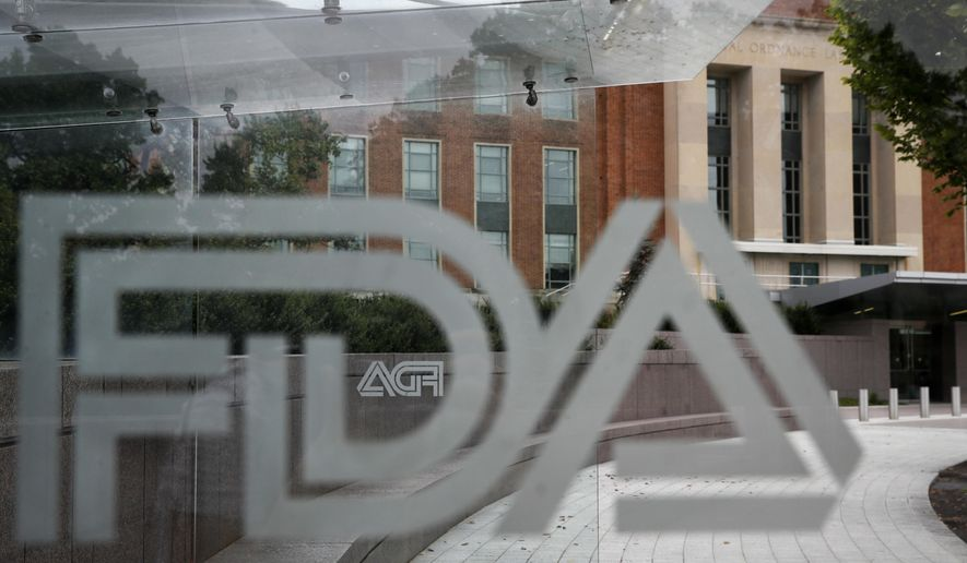 This Thursday, Aug. 2, 2018, file photo shows the U.S. Food and Drug Administration building behind FDA logos at a bus stop on the agency's campus in Silver Spring, Md. (AP Photo/Jacquelyn Martin, File)