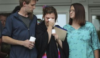 """In a Saturday, June 1, 2019 photo, Jessica Whipple, center, cries during a candlelight vigil in remembrance of her daughter, 5-year-old Elizabeth """"Lizzy"""" Shelley on the steps of the Historic Cache County Courthouse in Logan, Utah. Whipple's fiancee Detrich Black, left, and an unidentified woman comfort her. Shelley was abducted from her Logan home and found dead five days later in the backyard of a nearby residence. (Jeffery D. Allred/The Deseret News via AP)"""