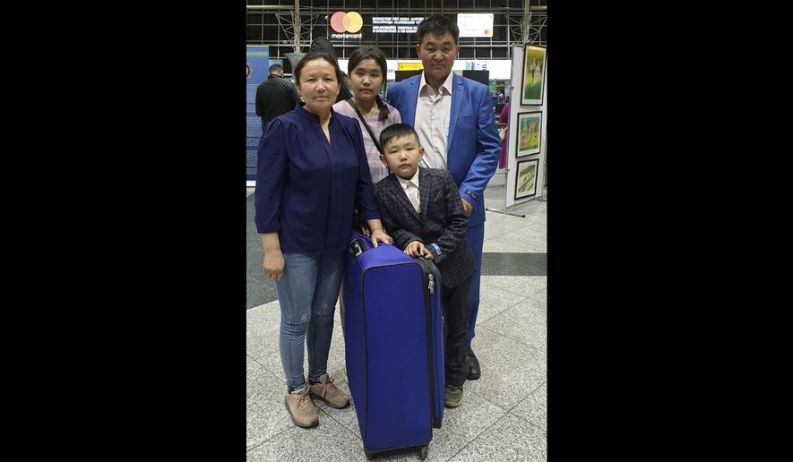 In this Sunday, June 2, 2019 photo taken by Aiman Umarova, Sayragul Sauytbay, left, Uali Sylam, her husband, right, and two children pose for a photo at an airport in Almaty, Kazakhstan, Sunday, June 2, 2019. The lawyer for a Chinese woman who attracted international attention after fleeing to Kazakhstan and speaking about working in Chinese internment camps says she has left the country for Sweden, where she expects to get political asylum. (Aiman Umarova via AP)