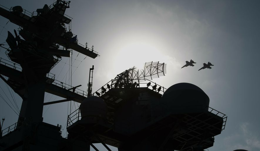 F/A-18 fighter jets fly over the deck of the USS Abraham Lincoln aircraft carrier in the Arabian Sea, Monday, June 3, 2019. The U.S. aircraft carrier the White House ordered to the Mideast over a perceived threat from Iran remains outside of the Persian Gulf amid efforts to de-escalate tensions between Tehran and Washington. (AP Photo/Jon Gambrell)