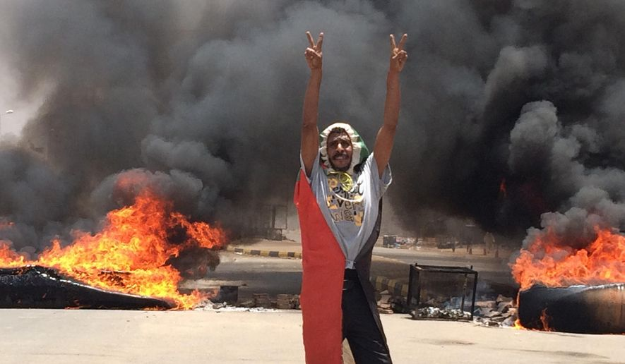 A protester flashes the victory sign in front of burning tires and debris on road 60, near Khartoum's army headquarters, in Khartoum, Sudan, Monday, June 3, 2019. Sudanese protest leaders say at least 13 people have been killed Monday in the military's assault on the sit-in outside the military headquarters in the capital, Khartoum. The protesters have announced they are suspending talks with the military regarding the creation of a transitional government. (AP Photo)