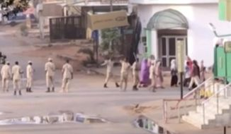 In this image made from video, Sudanese forces escort civilian in Khartoum, Sudan on Monday, June 3, 2019. Sudanese security forces moved against a protest sit-in camp in the capital Monday, witnesses and protest organizers said. Machine gun fire and explosions were heard and smoke rose from the area. Protest organizers said at least two people were killed.(AP Photo via AP video)
