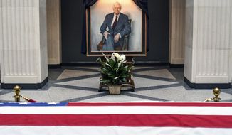 The body of former U.S. Senator Thad Cochran lies in state in front of a portrait of him at the Robert C. Khayat Law Center at the University of Mississippi in Oxford, Miss. on Sunday, June 2, 2019. Cochran died on Thursday in Oxford. (Bruce Newman/The Oxford Eagle via AP)