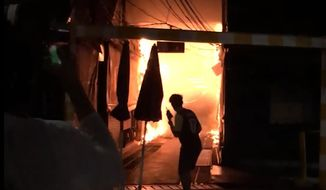 This Sunday, June 2, 2019 image taken from video provided by Younes Parvin shows a fire at Bangkok's Chatuchak weekend market, Thailand. Thai authorities are investigating an after-hours fire that roared through Chatuchak market, destroying dozens of the small shops crammed inside one of Asia's most popular bazaars. (Younes Parvin via AP Photo)