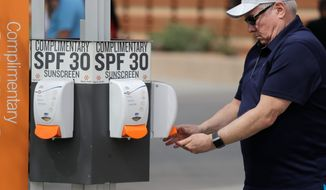 A fan get sunscreen from a complimentary kiosk before a spring training baseball game Wednesday, March 6, 2019, in Scottsdale, Ariz. (AP Photo/Elaine Thompson)