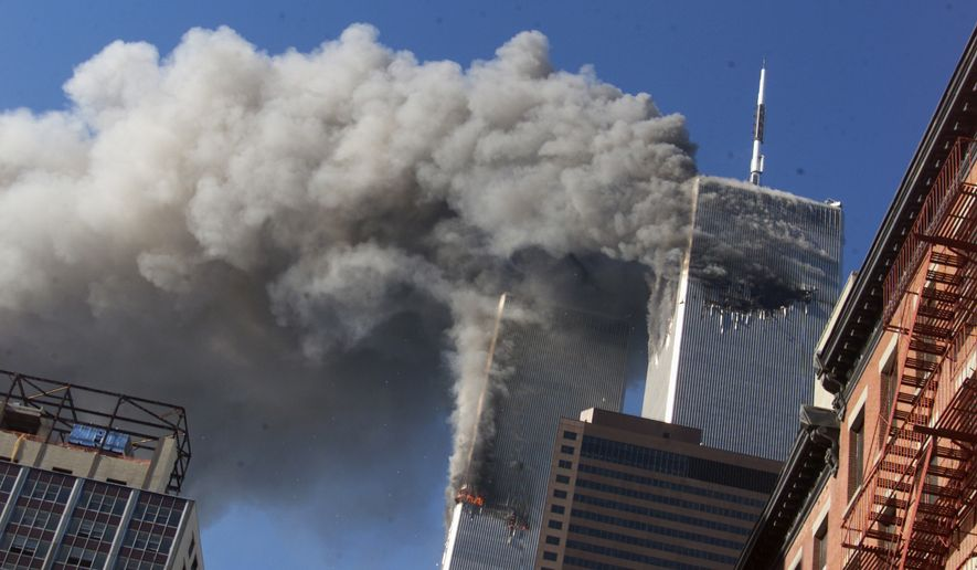 FILE - In this Sept. 11, 2001 file photo smoke rises from the burning twin towers of the World Trade Center after hijacked planes crashed into the towers, in New York City. On Friday, Feb. 15, 2019, Rupa Bhattacharyya, the September 11th Victim Compensation Fund special master, announced that the compensation fund for victims of the Sept. 11, 2001 terror attacks will cut future payments by 50 to 70 percent because the fund is running out of money. (AP Photo/Richard Drew, File) **FILE**