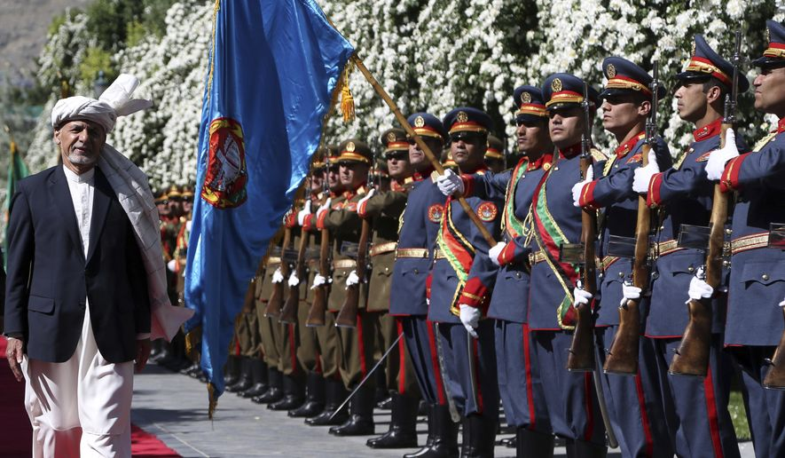 Afghanistan's President Ashraf Ghani, left, inspects the guard of honor as he prepares for Eid al-Fitr prayer at the presidential palace in Kabul, Afghanistan, Tuesday, June 4, 2019. Eid al-Fitr prayer marks the end of the holy fasting month of Ramadan in Afghanistan. (AP Photo/Rahmat Gul)