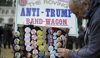 A man looks at badges with anti-Trump messages, on sale in central London, during a protest against the state visit of President Donald Trump, Tuesday, June 4, 2019. (AP Photo/Matt Dunham)