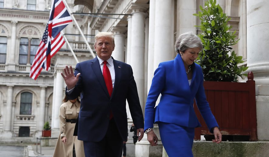 Britain's Prime Minister Theresa May and President Donald Trump walk through the Quadrangle of the Foreign Office for a joint press conference in central London, Tuesday, June 4, 2019. (AP Photo/Frank Augstein)