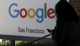 A woman walks past a Google sign in San Francisco, May 1, 2019. The U.S. Justice Department and the Federal Trade Commission are moving to investigate Google, Facebook, Amazon and Apple over their aggressive business practices, and the House Judiciary Committee has announced an antitrust probe of unidentified technology companies. (AP Photo/Jeff Chiu) ** FILE **
