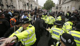 Police forces are trying to restore order after a small scuffle broke out between Donald Trump supporters and people that gathered in central London to demonstrate against the state visit of President Donald Trump, Tuesday, June 4, 2019. Trump will turn from pageantry to policy Tuesday as he joins British Prime Minister Theresa May for a day of talks likely to highlight fresh uncertainty in the allies' storied relationship. (AP Photo/Tim Ireland)