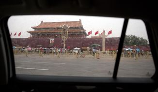 The large portrait of former Chinese leader Mao Zedong on Tiananmen Gate next to Tiananmen Square is seen through the window of car in Beijing, Tuesday, June 4, 2019. Chinese authorities stepped up security Tuesday around Tiananmen Square in central Beijing, a reminder of the government's attempts to quash any memories of a bloody crackdown on pro-democracy protests 30 years ago. (AP Photo/Mark Schiefelbein)