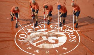 Stadium workers remove water from the court cover after rain interrupted quarterfinal matches of the French Open tennis tournament at the Roland Garros stadium in Paris, Tuesday, June 4, 2019. (AP Photo/Jean-Francois Badias)