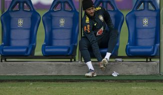 Brazil's Neymar puts on his cleats during a practice session of the national soccer team at the Granja Comary training center ahead the Copa America tournament in Teresopolis, Brazil, Tuesday, June 4, 2019. (AP Photo/Leo Correa)