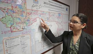 In this Monday, June 3, 2019, photo, Orange County Commissioner Emily Bonilla looks at a map of Orange County and the city of Orlando in Orlando, Fla. Bonilla is worried her district in metro Orlando will be undercounted during next spring's once-in-a-decade head count of everybody in the United States because of who lives there: new arrivals, immigrants, the poor, renters and people living in rural areas who sometimes regard government with suspicion. (AP Photo/John Raoux)