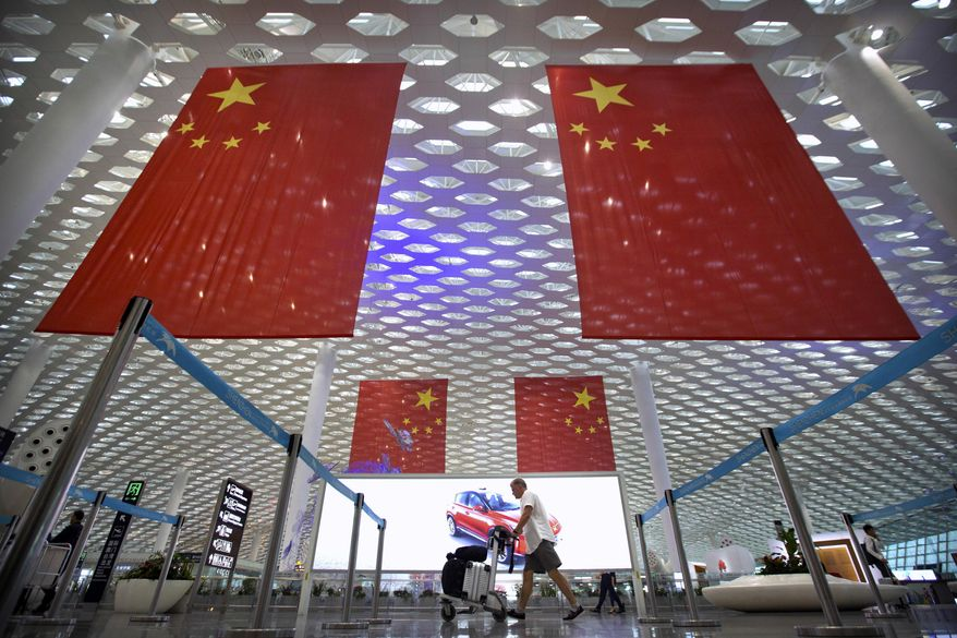 In this Oct. 10, 2018, file photo, a traveler pushes his luggage beneath large Chinese flags hanging from the ceiling in Shenzhen Bao'an International Airport in Shenzhen in southern China's Guangdong province. China has on Tuesday, June 4, 2019, issued a travel warning for the U.S., saying Chinese visitors have been interrogated, interviewed and subjected to other forms of what it called harassment by U.S. law enforcement agencies. (AP Photo/Mark Schiefelbein) **FILE**