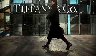 FILE- In this Nov. 29, 2018, file photo, a woman walks past a Tiffany & Co. store at a shopping mall in Beijing. Tiffany & Co. reports financial results on Tuesday, June 4, 2019. (AP Photo/Mark Schiefelbein, File)