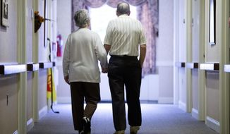 In this Nov. 6, 2015 file photo, an elderly couple walks down a hall of a nursing home in Easton, Pa. Three nursing home workers in North Carolina were arrested in Oct. 2019 after they allegedly encouraged dementia patients to fight each other. (AP Photo/Matt Rourke, File) **FILE**