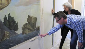Devin Colman, foreground, of the Vermont Division of Historic Preservation and Janie Cohen, director of the Fleming Museum at the University of Vermont, look at the signature on a painting of a prominent Lake Champlain geological formation, Tuesday June 4, 2019, in Burlington, Vt. The painting of the Rock Point Overthrust was created by Vermont artist Raymond Pease as part of the Public Works Art Project, which employed artists during the Great Depression. It was deliberately covered up in the early 1990s because officials didn't have the money to conserve it. Now plans are in place to move the painting and conserve it. (AP Photo/Wilson Ring)