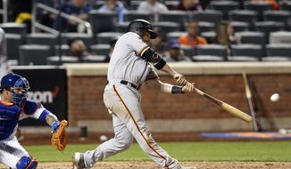 San Francisco Giants Stephen Vogt hits a two-run double during the tenth inning of a baseball game against the New York Mets, Tuesday, June 4, 2019, in New York. New York Mets catcher Wilson Ramos is behind the plate. (AP Photo/Kathy Willens)