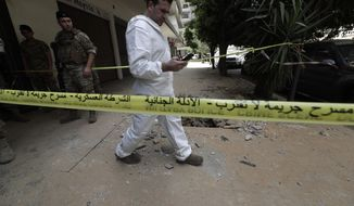 A Lebanese Army investigator checks his mobile phone outside a building where clashes erupted between Lebanese troops and a a former member of the Islamic State group, who had engaged in an hours-long shootout with the security forces, Tripoli, Lebanon, Tuesday, June 4, 2019. Lebanon's interior minister said Tuesday, that a lone gunman who went on a shooting spree in the northern city of Tripoli, killing four security personnel, was working alone. (AP Photo/Hassan Ammar)