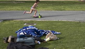 In this Monday, June 3, 2019 photo a child rides her scooter past a homeless person covered under a blanket in Santa Monica, Calif. The number of homeless people counted across Los Angeles County jumped 12% over the past year to a total of 58,936. The Los Angeles Homeless Services Authority presented the results of January's annual count to the Board of Supervisors on Tuesday, June 4.  (AP Photo/Richard Vogel)