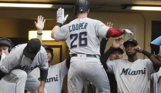 Miami Marlins' Garrett Cooper is congratulated after hitting a home run during the third inning of a baseball game against the Milwaukee Brewers Tuesday, June 4, 2019, in Milwaukee. (AP Photo/Morry Gash)
