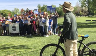 In this Saturday, June 1, 2019 photo, a passing bicyclist pauses to watch supporters of Denver Mayor Michael Hancock as they pause for a picture during a rally for the incumbent in Denver. Hancock, who is seeking his third, four-year term as mayor, is facing Jamie Giellis in a runoff Tuesday. (AP Photo/James Anderson)