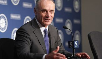 Baseball Commissioner Rob Manfred talks to reporters before a baseball game between the Seattle Mariners and the Houston Astros on Tuesday, June 4, 2019, in Seattle. (AP Photo/Elaine Thompson) ** FILE **
