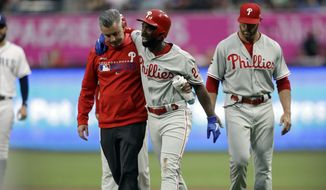 Philadelphia Phillies' Andrew McCutchen, center, is helped by a trainer after being injured while trying to get back to first base during the first inning of a baseball game against the San Diego Padres Monday, June 3, 2019, in San Diego. Phillies manager Gabe Kapler, right, looks on. (AP Photo/Gregory Bull) **FILE**