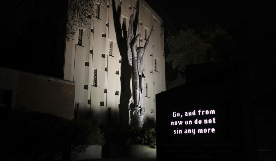 "An illuminated sign outside St. Michael Archangel Catholic Church in Houston reads, ""Go, and from now on do not sin any more"" on April 11, 2019. The church, which has been grappling for decades with the sexual abuse of children, is now being forced to reckon with the recognition that adults too can be sexually exploited by clergy. (AP Photo/Wong Maye-E)"