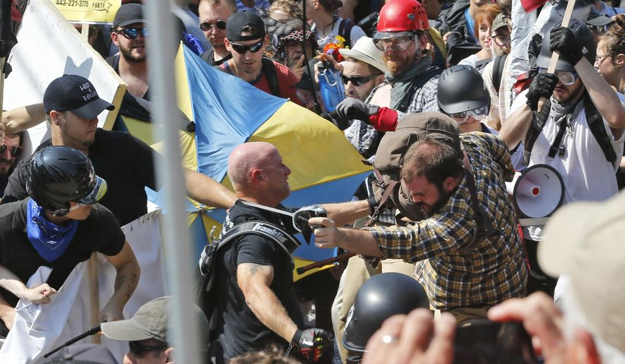 FILE - In this Aug. 12, 2017 file photo, white nationalist demonstrators clash with counter demonstrators at the entrance to Lee Park in Charlottesville, Va. Federal charges against three alleged members of a violent white supremacist group accused of inciting violence at California political rallies were dismissed Monday, June 3, 2019, by Judge Cormac J. Carney in U.S. District Court in Los Angeles, who found their actions amounted to constitutionally protected free speech. (AP Photo/Steve Helber, File)
